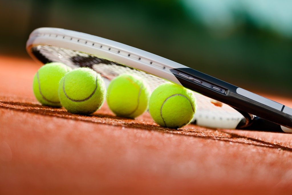 Tennis racket and balls on the clay tennis court