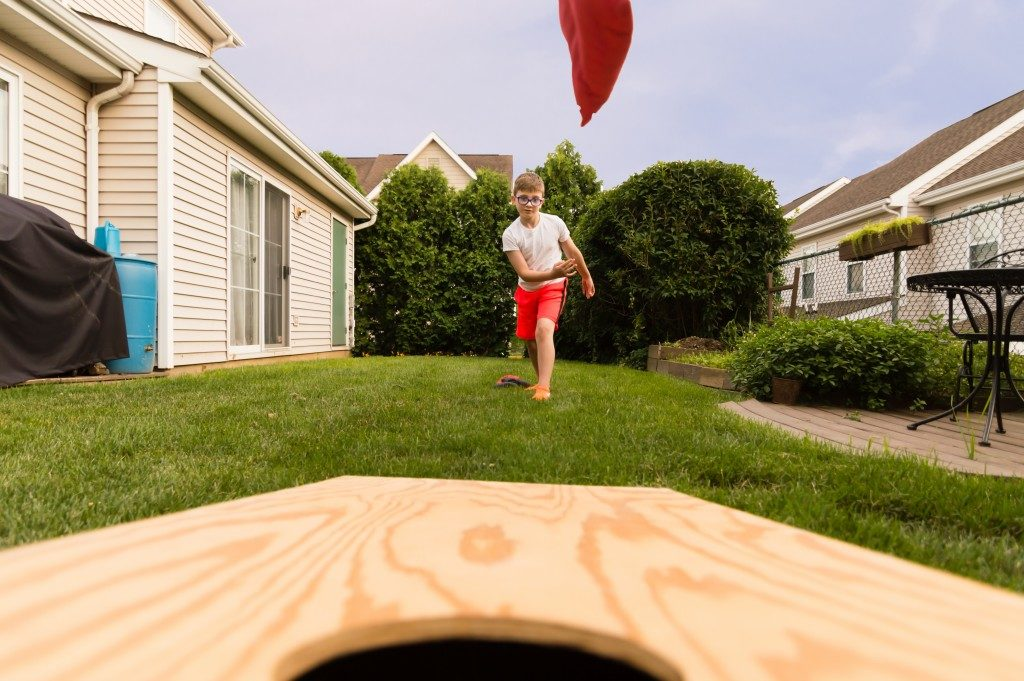 Kid playing cornhole game